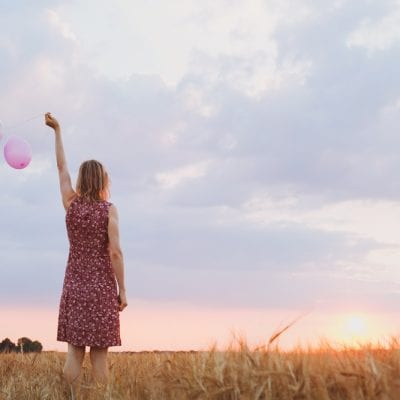 Woman letting go of balloons